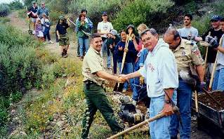 Mike Boulland shaking hands with park ranger Chris, who helps maintain...
